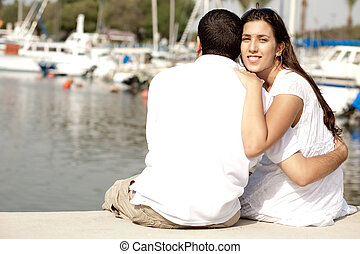 Young Couple Seated and Hugging On A Footbridge