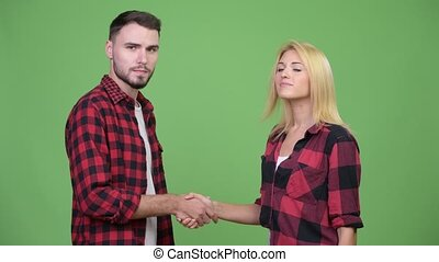 Young couple shaking hands together - Studio shot of young...