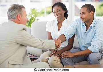 Young couple shaking hands with salesman on the couch in the office