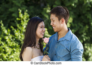 Young couple sharing a pink rose