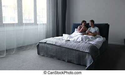 Young couple sharing breakfast in bed at home - Beautiful...