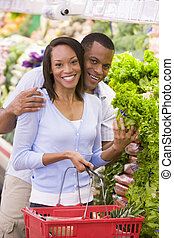Young couple shopping for lettuce at a grocery store
