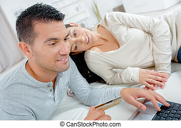 young couple shopping online at home on laptop