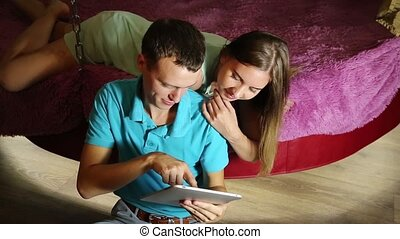 Young couple shopping online using digital tablet computer. Couple laughing, girl lying on the bed at home and guy sitting next to on the floor