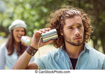 Young couple shouting through tin cans on a summers day