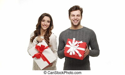 Young couple showing and giving present to camera on white...