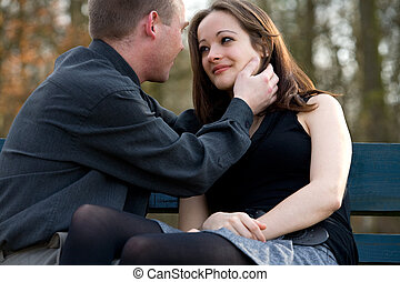 Young couple showing love - Man and girlfriend on a bench in...