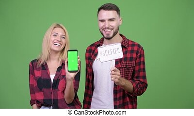 Young couple showing phone while holding selfie paper sign...