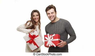 Young couple showing presents in Chrismas day on white background.