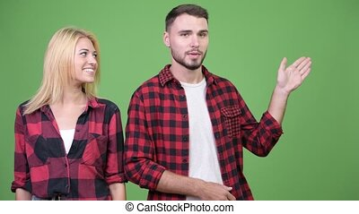 Young couple showing something and talking to camera...