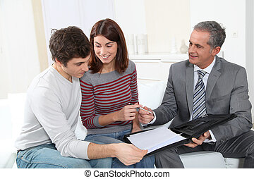 Young couple sigining renting contract with real estate...