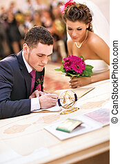Young couple signing wedding documents. Focus on hand.