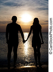 Young couple silhouette on a sea beach holding hands and...