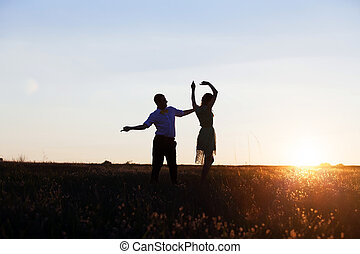 Young couple silhouettes dancing on the field