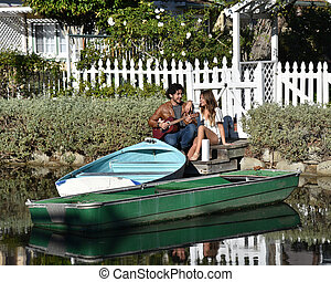 Young couple singing by boats in a river