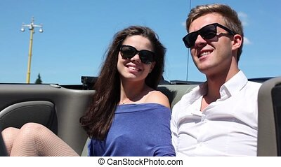 Young couple sit and talk in cabriolet at sunny summer day