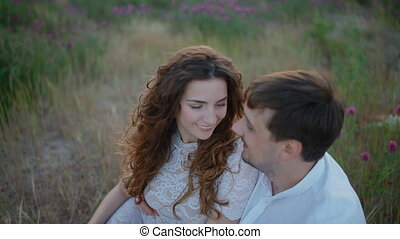 Young couple sit in the field