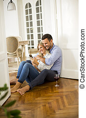 Young couple sits on the floor, drinking red wine and woman using cell phone