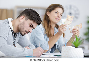 young couple sitting and calculating bills at home