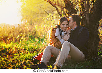 Young couple sitting and kissing near the tree in the forest
