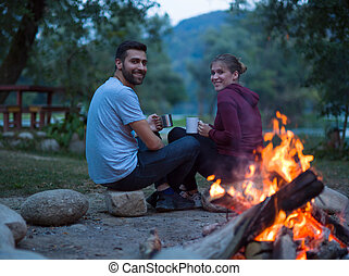 couple sitting around the campfire at evening