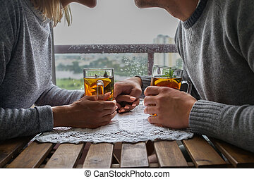 Young couple sitting at a table, with the care relate to each other in the rain outside the window. warm relations on a date