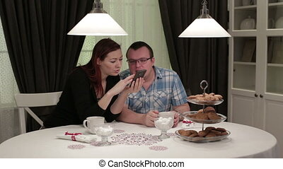 Young couple sitting at the table doing selfie