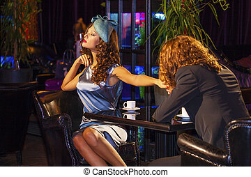 Young couple sitting in a nightclub at the table