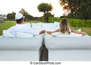 Young couple sitting in armchair and holding hands together
