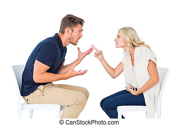 Young couple sitting in chairs arguing