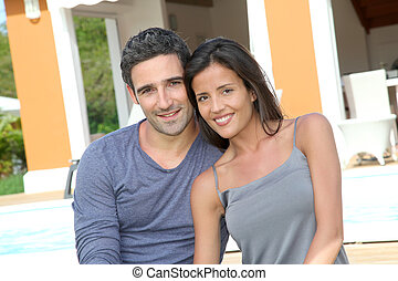 Young couple sitting in front of brand new home
