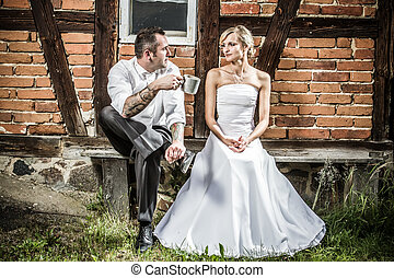 Young couple sitting in front of the old house on a bench