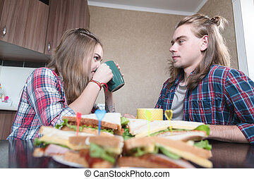 Young couple sitting in kitchen, drinking from cups, chatting. Closeup