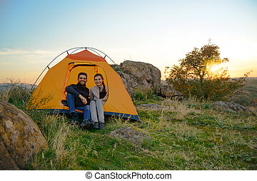 Young Couple Sitting near Tent at Beautirul Evening in the Mountains. Adventure and Family Travel.