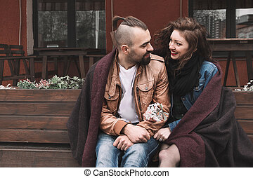 young couple sitting on a bench in the old city street.