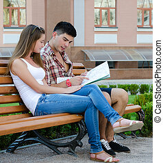 Young couple sitting on a bench reading a map