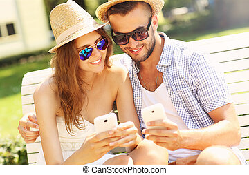 Young couple sitting on a bench with smartphones