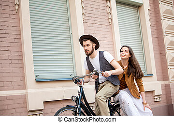 Young couple sitting on a bicycle against the wall in town