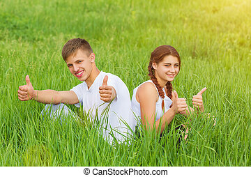young couple sitting on a green meadow