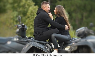 young couple sitting on a quad bike