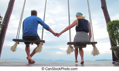 Young couple sitting on a swing admiring nature