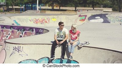 Young couple sitting on a wall at a skate park