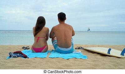 Young couple sitting on beach 4k - Rear view of young couple...