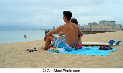 Young couple sitting on beach 4k