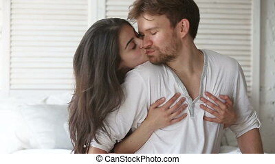 Young couple sitting on bed, beautiful woman embracing man