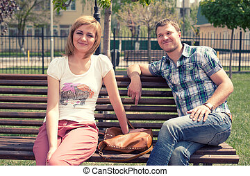 Young couple sitting on bench in park