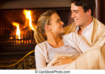 young couple sitting on couch at home