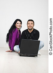 Young couple sitting on floor with laptop