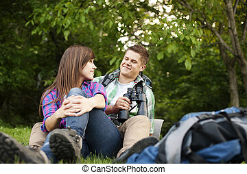 Young couple sitting on glade