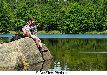 Young couple sitting on rock by the lake